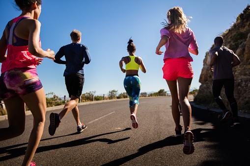 Team of athletes running outdoors on summer stock photo
