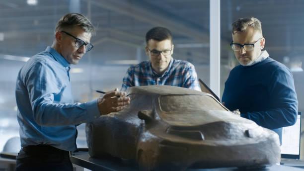 automobil-design-ingenieure diskutiert neue prototypmodell aus plastilin ton. sie arbeiten in einem großen automobilwerk. - prototype stock-fotos und bilder