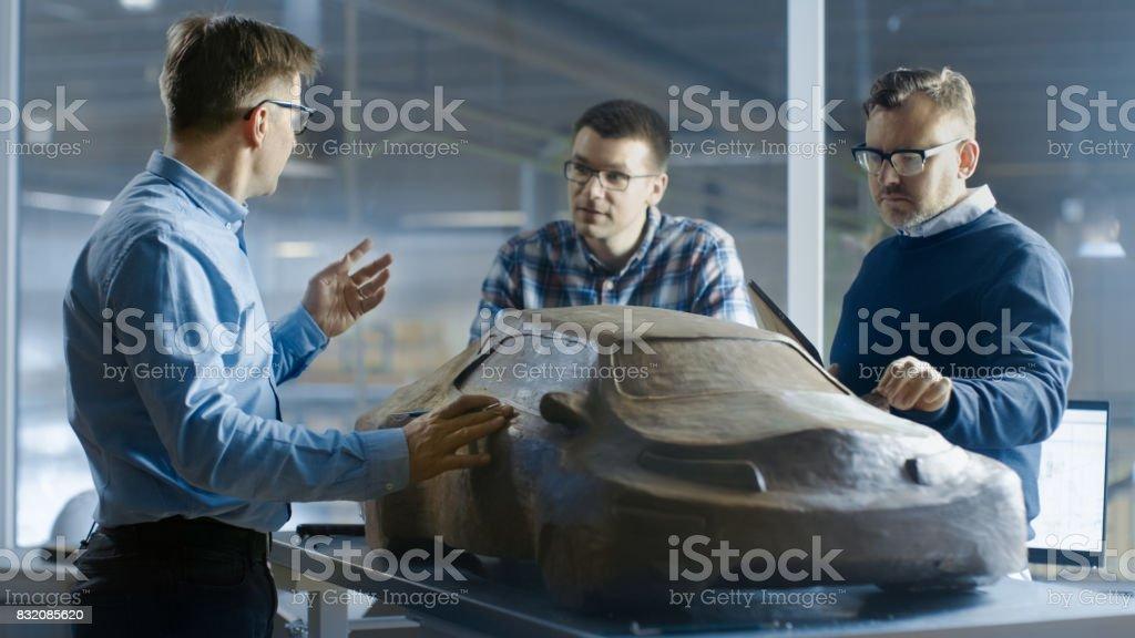 Automobil-Design-Ingenieure diskutiert neue Prototypmodell aus Plastilin Ton. Sie arbeiten in einem großen Automobilwerk. – Foto