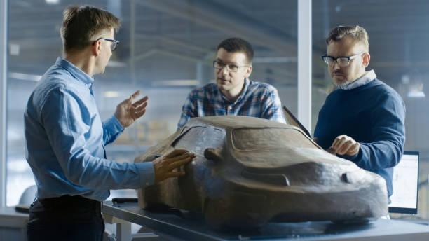 automobil-design-ingenieure diskutiert neue prototypmodell aus plastilin ton. sie arbeiten in einem großen automobilwerk. - skulpturprojekte stock-fotos und bilder