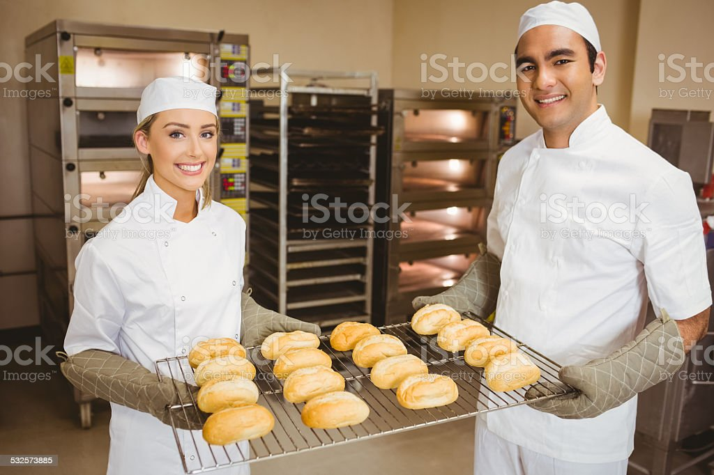 Team of bakers holding rolls stock photo