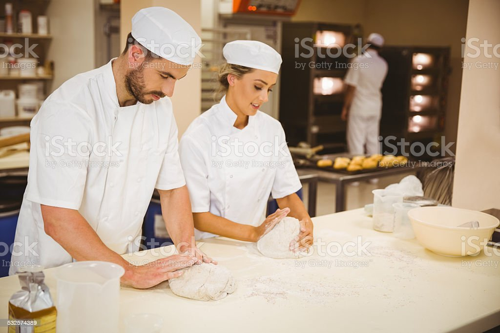 Team of bakers kneading dough stock photo