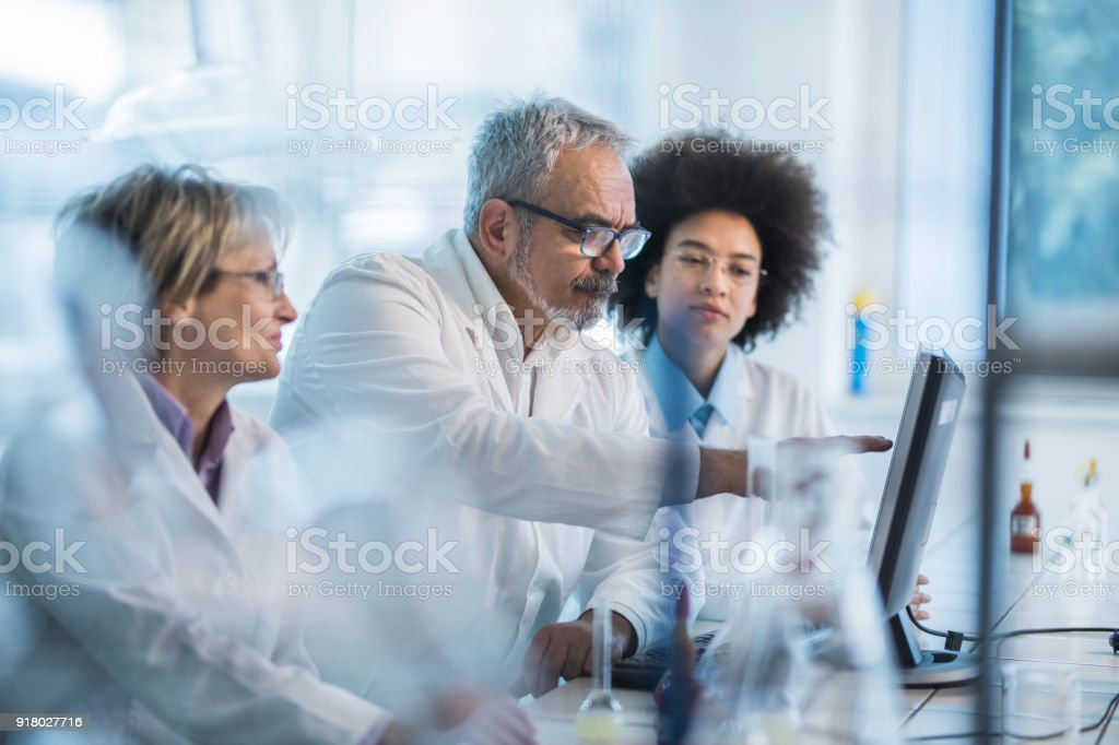 Team of biotechnologists working on desktop PC in laboratory. stock photo