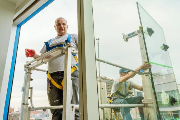 Team von Arbeitern ersetzt ein zerbrochenes Fenster im Bürogebäude - mit einem frischen Dichtstoff für eine neue Glasinstallation. Höhenarbeiten an der Hebebühne, die draußen platziert ist. – Foto