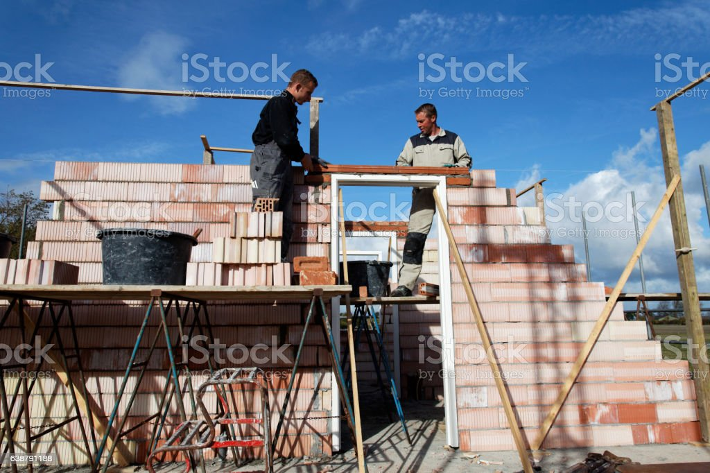 Team of bricklayers putting a lintel under blue sky stock photo