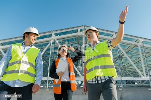681242254 istock photo Team of builders engineer architect on the roof of construction site. Building, development, teamwork and people concept 1130462572
