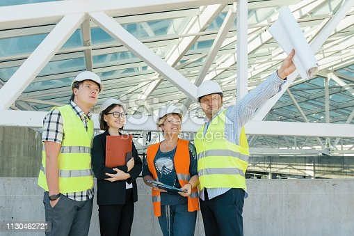 1129095769 istock photo Team of builders engineer architect on the roof of construction site. Building, development, teamwork and people concept 1130462721