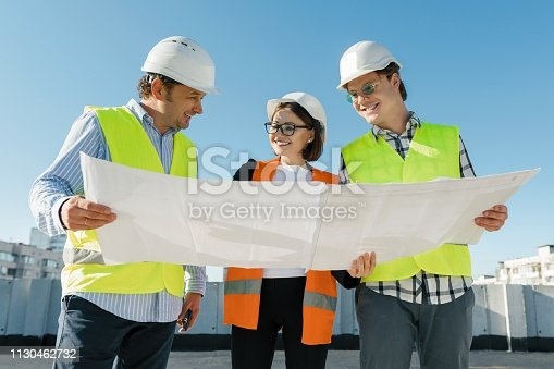 681242254 istock photo Team of builders engineer architect on the roof of construction site. Building, development, teamwork and people concept 1130462732