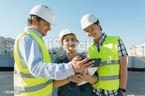 681242254 istock photo Team of builders engineer architect on the roof of construction site. Building, development, teamwork and people concept 1130462752