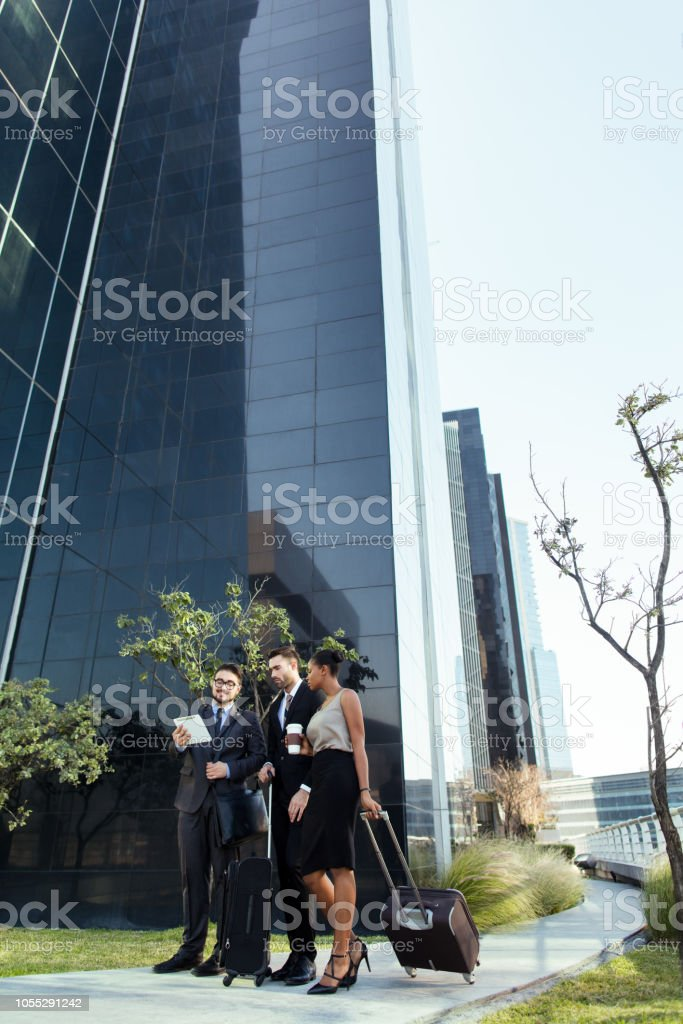 Team of business executives talking outside of building stock photo