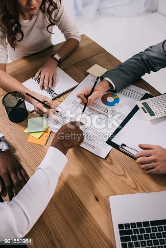 istock Team of business partners doing paperwork while sitting at table 961552954