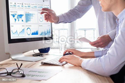istock Team of business people discussing digital marketing metrics report and return on investment strategy for advertisement campaign, data analytics dashboard on computer screen in office 963146264