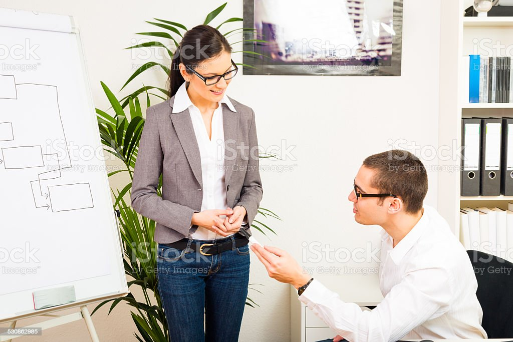 team of business people discussing over a gantt chart stock photo