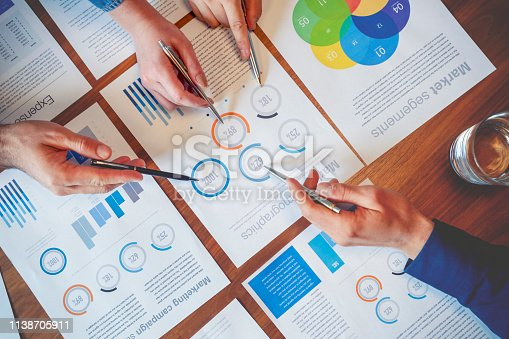 Team of business people point to numbers on financial data. Teamwork concept paperwork and graphs and charts. High angle view of hands using pens to point.