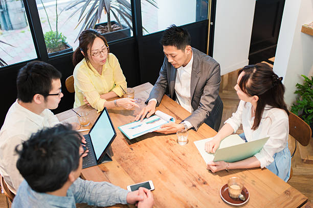Team of businessmen and women around a table Five business people around a table having a business meeting. Kyoto, Japan. May 2016 only japanese stock pictures, royalty-free photos & images