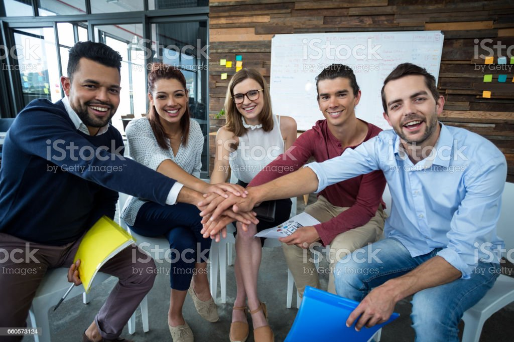 Team of businesspeople forming hand stack in office stock photo