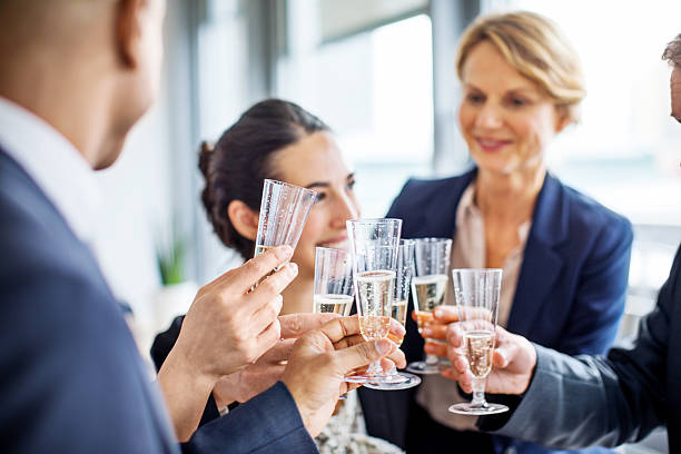 team of businesspeople toasting champagne - fête de bureau photos et images de collection