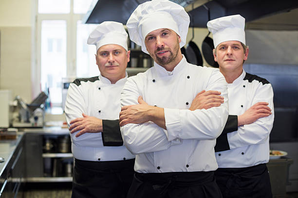 Team of chefs in the kitchen Team of chefs in the kitchen chef's whites stock pictures, royalty-free photos & images