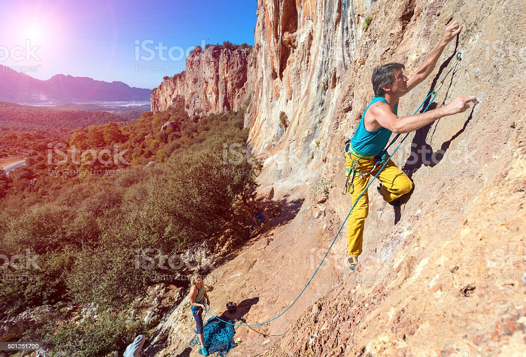 Team of Climbers ascending orange rocky Wall with Sun stock photo
