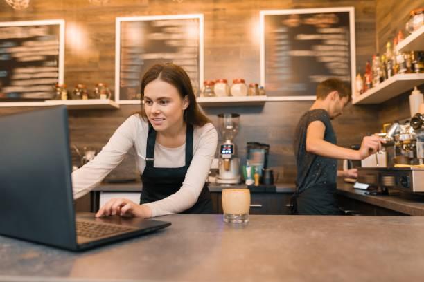 Equipo de trabajadores de la cafetería trabajando cerca del mostrador con ordenador portátil y un café, negocio de café - foto de stock