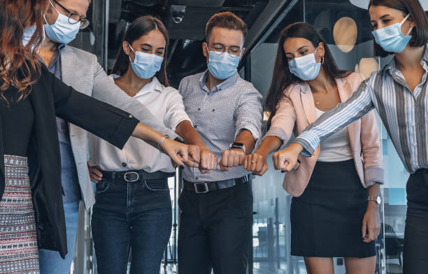 Team of colleagues with face mask joining their hands together in unity during pandemic stock photo