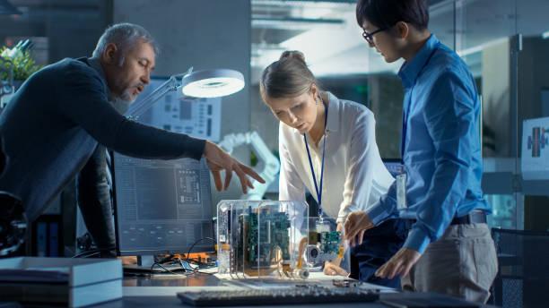equipo de ingenieros informáticos se apoye sobre el escritorio y elija tableros del circuito impreso para trabajar con, computadora muestra programación en curso. en el fondo tecnológicamente había avanzado centro de investigación científica. - ingeniero fotografías e imágenes de stock