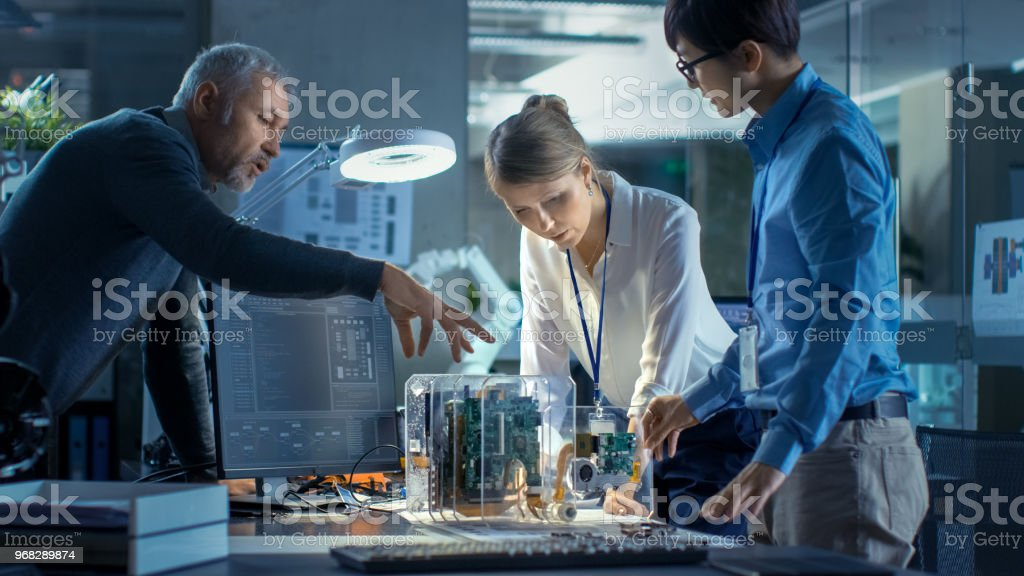 Team of Computer Engineers Lean on the Desk and Choose Printed Circuit Boards to Work with, Computer Shows Programming in Progress. In The Background Technologically Advanced Scientific Research Center. stock photo