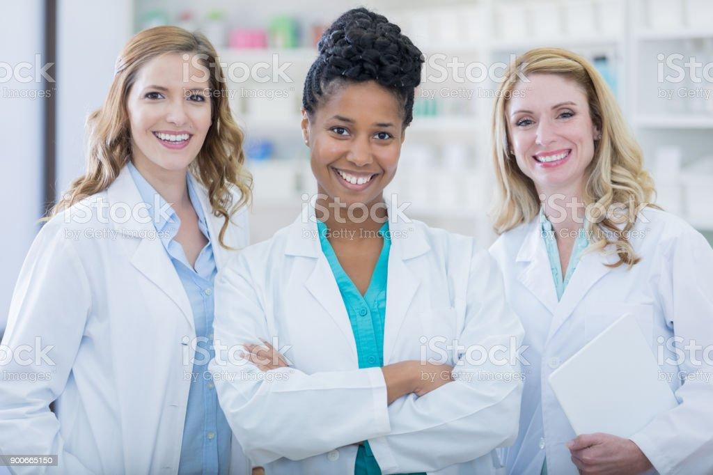 Team of confident female pharmacists smiling for photo in neighborhood pharmacy stock photo