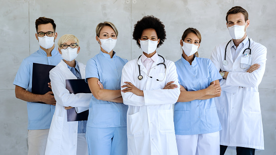 Group of healthcare workers wearing protective face masks while standing with arms crossed and looking at camera.