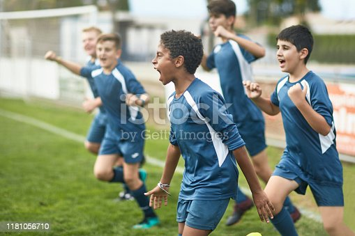 Energetic preteen and teenage male footballers cheering and punching the air as they run onto field for training session.