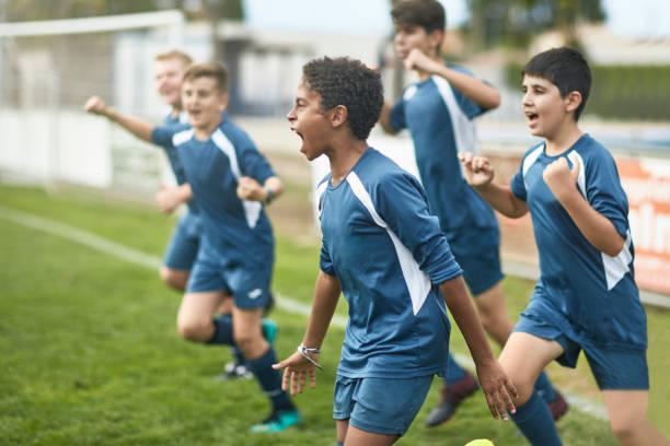zespół pewnych siebie młodych piłkarzy biegających na boisko - kultura młodości zdjęcia i obrazy z banku zdjęć