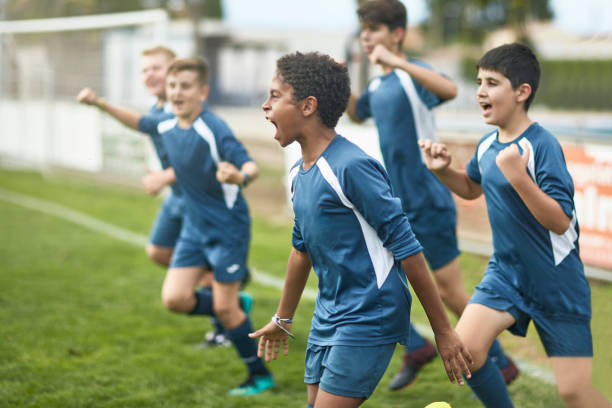 Team of Confident Young Male Footballers Running Onto Field stock photo