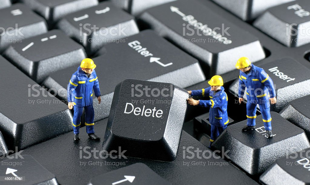 Team of construction workers working on a computer keyboard Team of construction workers working with DELETE button on a computer keyboard Business Stock Photo