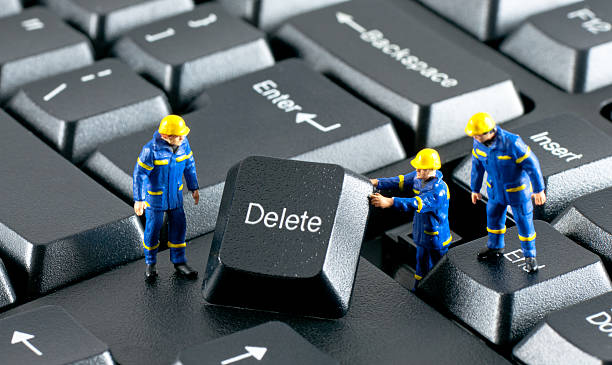 team of construction workers working on a computer keyboard - delete key stock photos and pictures