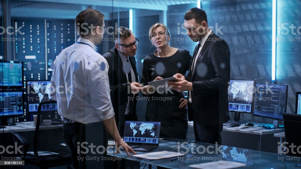 Team of Corporate Managers Having Meeting in Monitoring Room. They're in State of the Art Facility. Computers have Animated Screens. stock photo