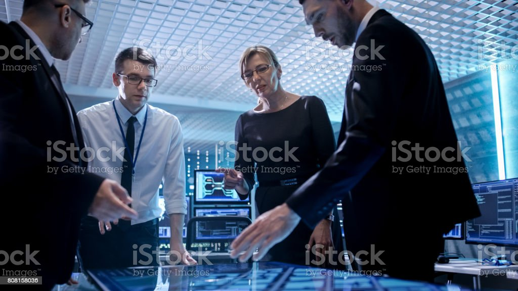 Team of Corporate Managers Working at the Table in Monitoring Room.  They're in State of the Art Facility. Computers have Animated Screens. - Royalty-free Adult Stock Photo