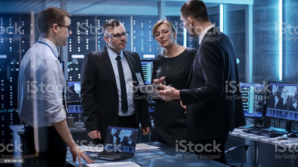 Team of Corporate Managers Working at the Table in Monitoring Room. They're in State of the Art Facility. Computers have Animated Screens. stock photo