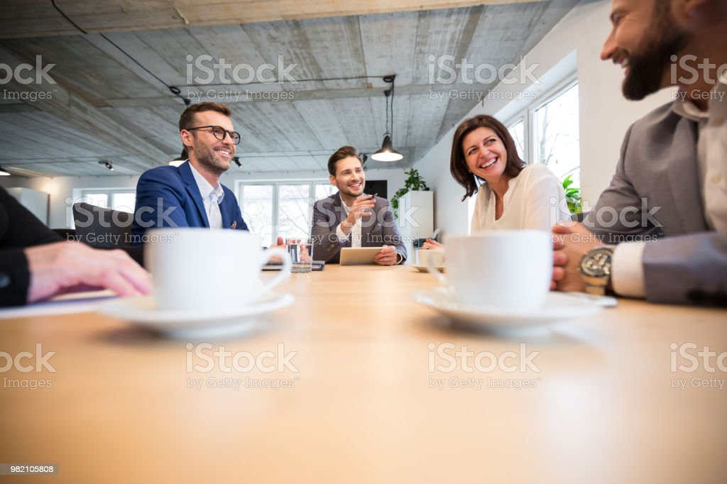 Team of corporate professionals in a meeting Team of corporate professionals having friendly discussion in a meeting. Executives talking and smiling during a meeting. Adult Stock Photo