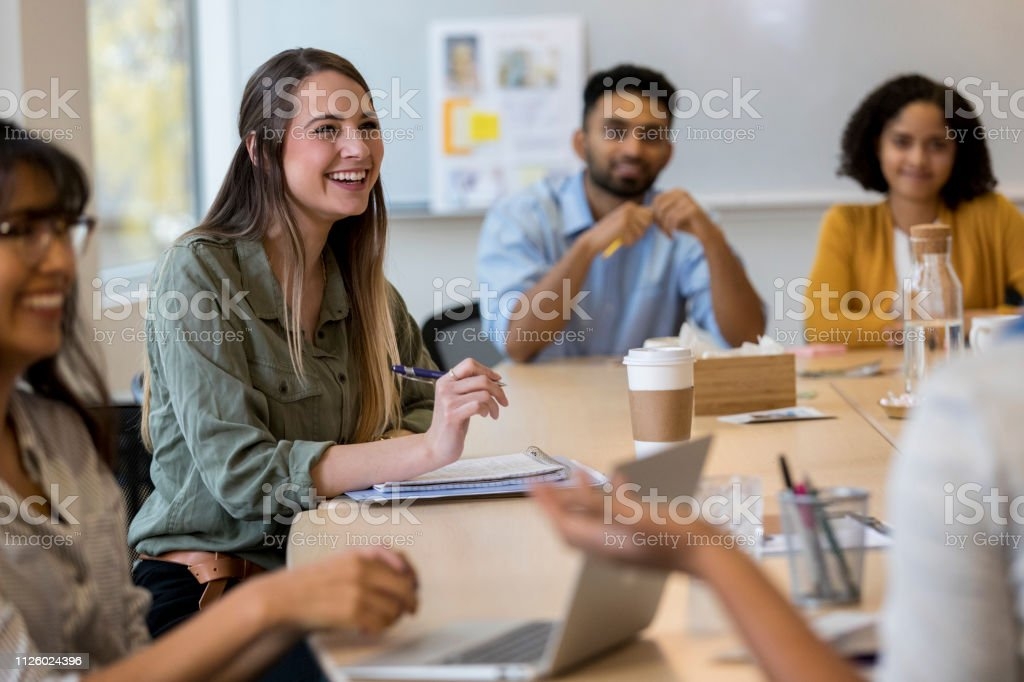 A cheerful team of design professional sit at a conference table and...