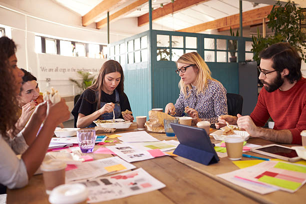 Team Of Designers Having Working Lunch Meeting In Office stock photo