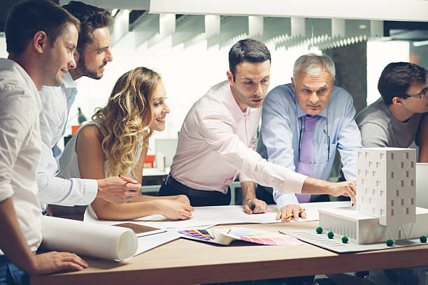 Team of designers reviewing architectural model in the office. stock photo