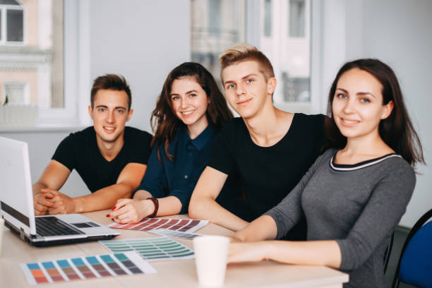team of designers sitting together at studio stock photo