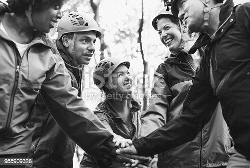Team of diverse hikers stacking hands together