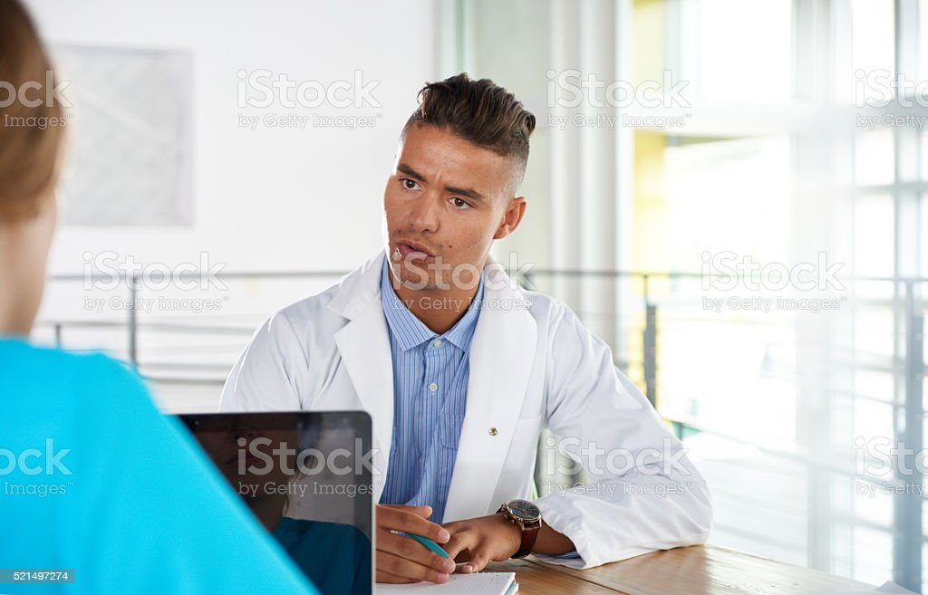 Team of doctor and nurse discussing a patient diagnosis sitting stock photo