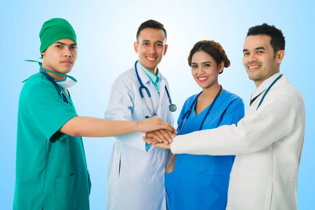Team of doctor and nurse putting their hands together with stethoscopes over isolated blue background. Team with stack of hands showing unity and teamwork. stock photo