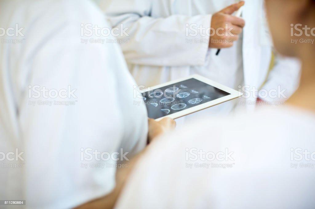 Team von Ärzten, die Analyse von MRI scans auf digital-Tablette - Lizenzfrei Analysieren Stock-Foto