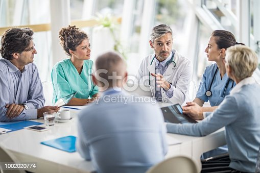Male doctor and his female colleagues talking to team of business people on a meeting in the hospital.