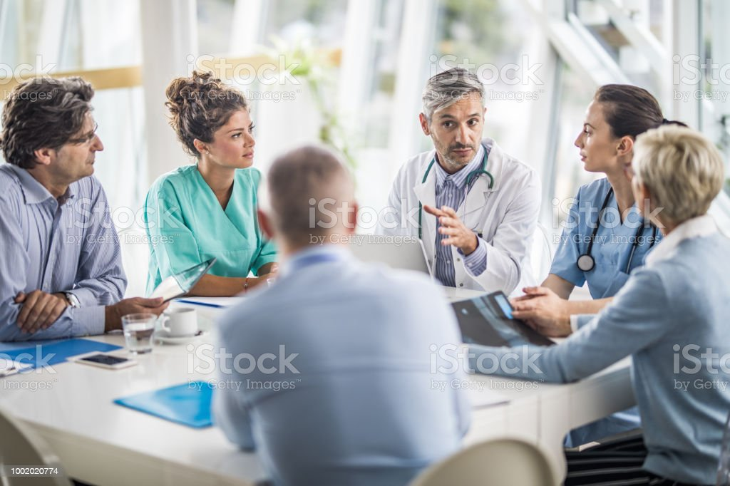 Team of doctors and business people talking on a meeting at doctor's office. stock photo
