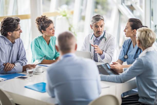 equipe de médicos e pessoas de negócios, falando em uma reunião no gabinete do médico. - profissional da área médica - fotografias e filmes do acervo