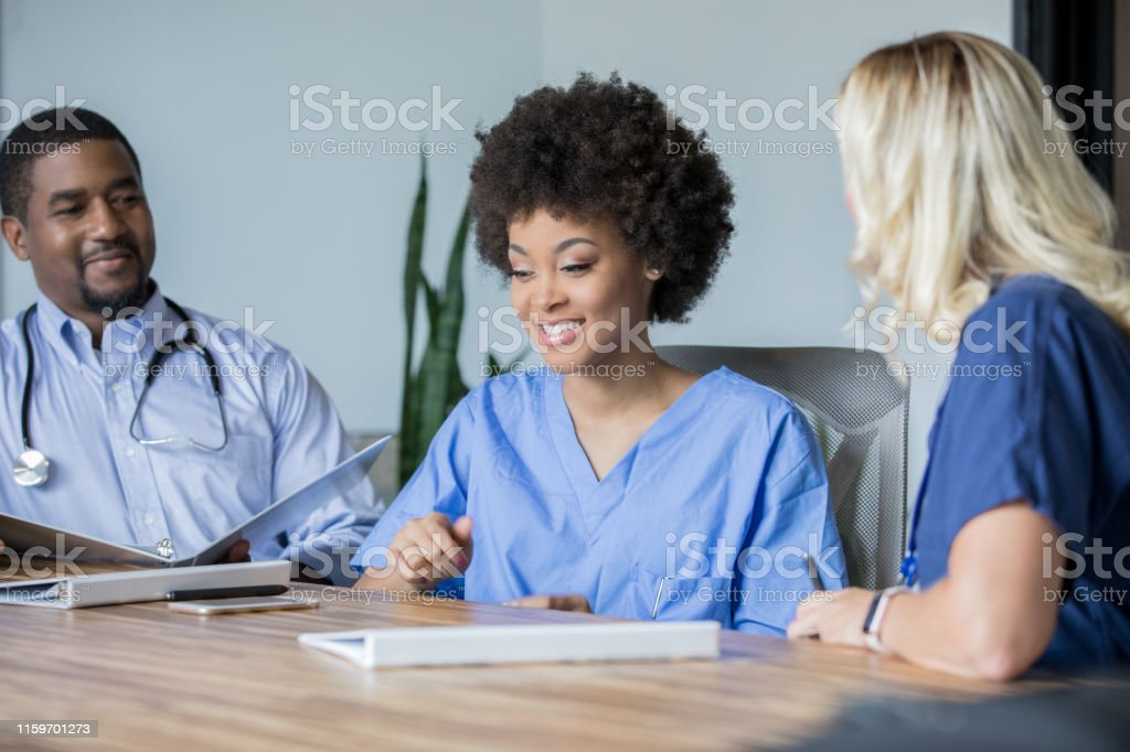 Team of doctors and medical professionals discuss patient diagnosis...